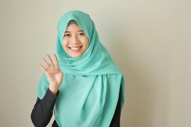 Femme pointant le numéro 4 vers le haut, modèle de femme musulmane asiatique