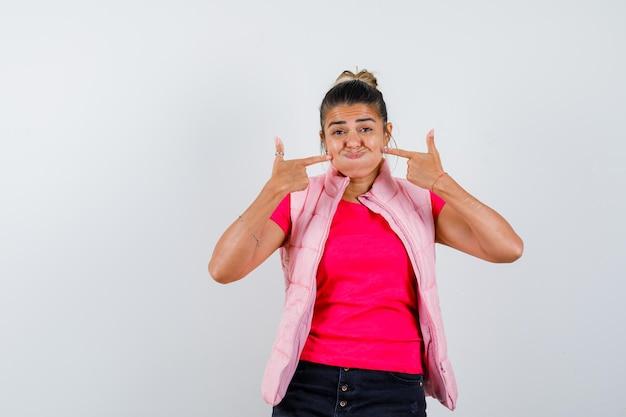 Femme pointant sur ses joues soufflées en t-shirt, gilet et à la rêveuse
