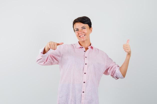 Femme pointant son pouce vers le haut en chemise rose et à la joyeuse. vue de face.
