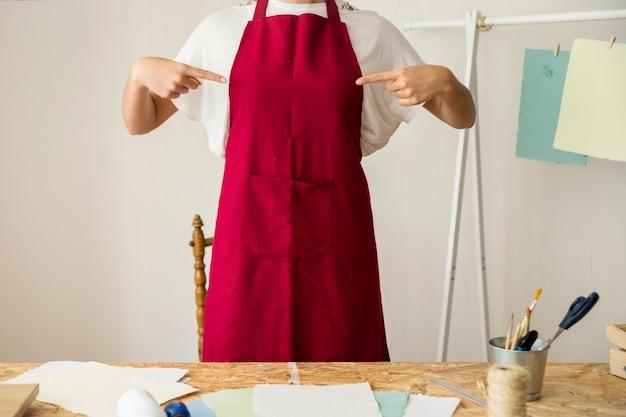 Femme pointant sur son tablier rouge