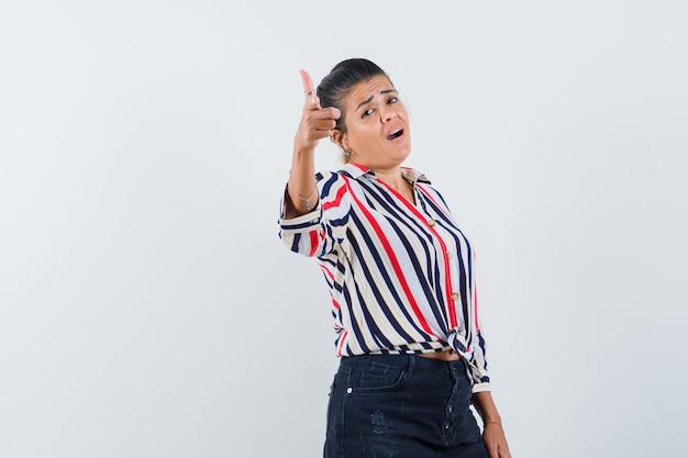 Femme pointant vers l'avant en chemise, jupe et à la confiance