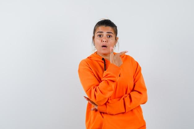 Femme pointant vers le côté droit en sweat à capuche orange et à la surprise