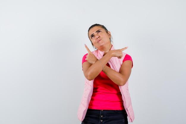 Femme pointant vers l'extérieur en t-shirt, gilet et à l'espoir