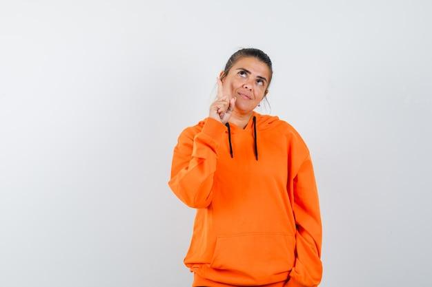 Femme pointant vers le haut en sweat à capuche orange et à la mignonne