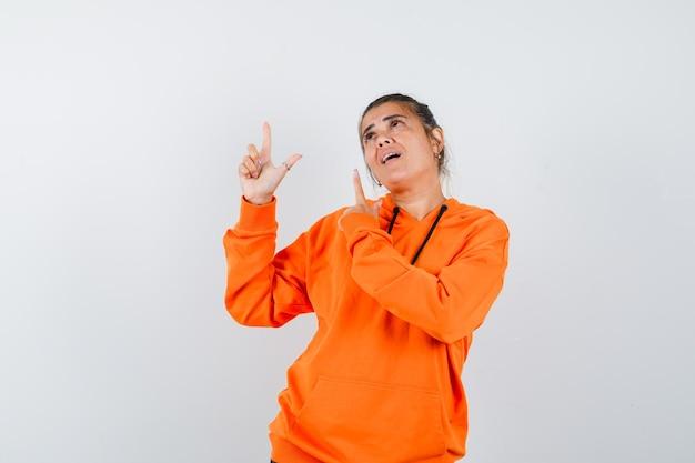 Femme pointant vers le haut en sweat à capuche orange et à la recherche de rêve