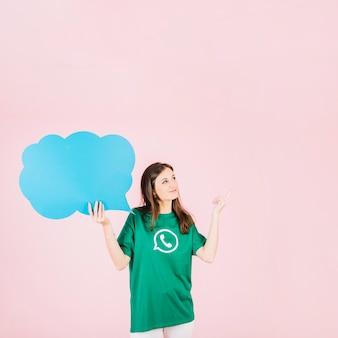 Femme pointant vers le haut tenant une bulle bleue vide