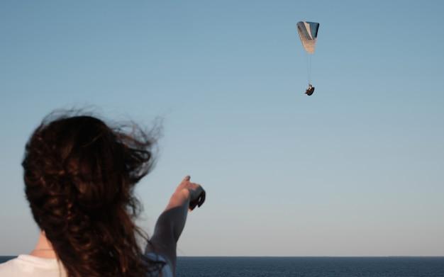 La femme pointe vers le parapente volant