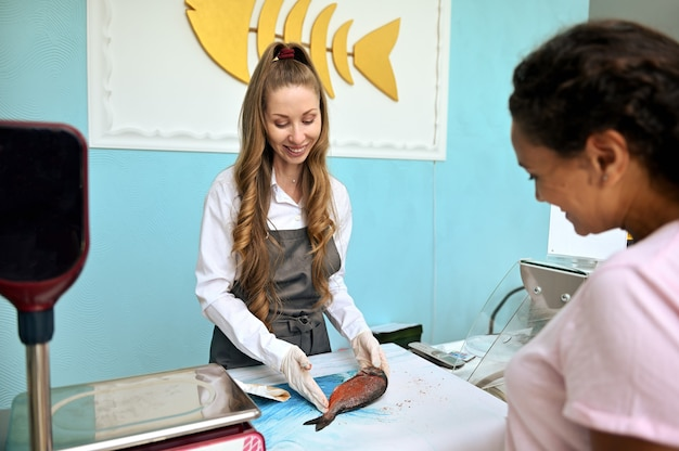 Femme de poisson souriante derrière un comptoir dans un magasin de fruits de mer, saupoudrant du poisson dorado avec différentes épices et servant le client.