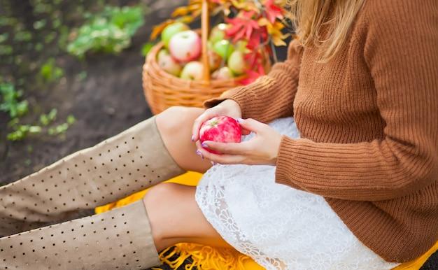 Femme avec une pomme mûre dans une main, assise sur une couverture jaune