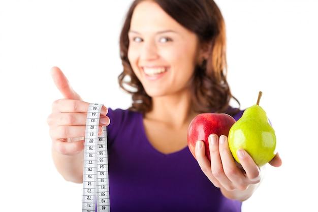 Femme avec pomme, poire et ruban à mesurer