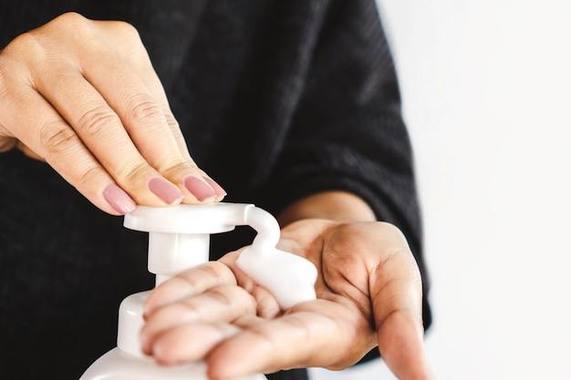 Femme pompe du savon liquide pour nettoyer sa main