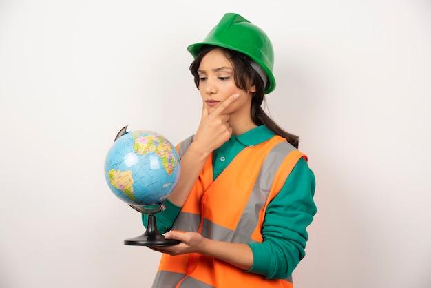Femme pompier regardant globe avec une expression sérieuse sur fond blanc.