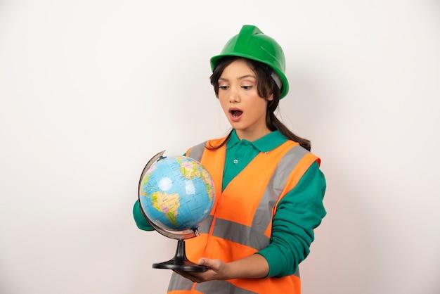Femme pompier regardant globe avec expression surprise.