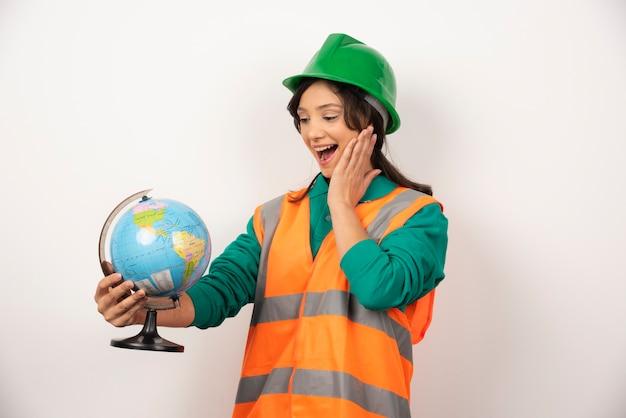 Femme pompier regardant globe sur fond blanc.