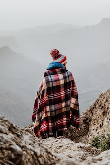 Femme avec poncho à carreaux et bonnet pompon donnant sur un magnifique paysage de montagne