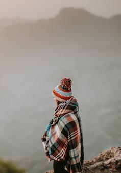 Femme avec poncho en regardant les montagnes