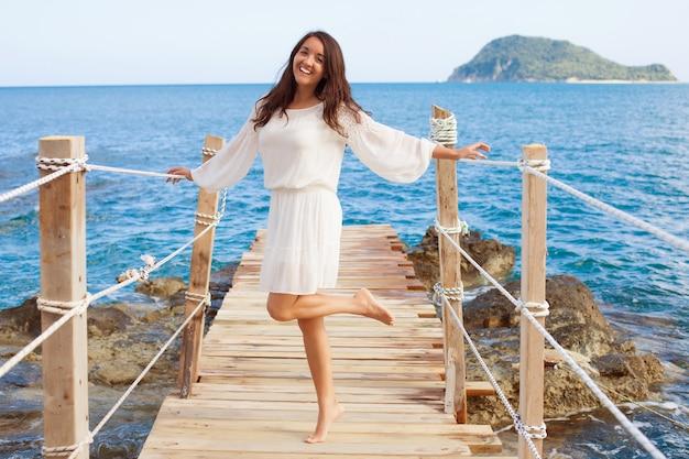 Femme sur le pont près de la mer