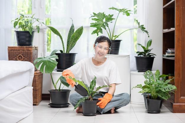 La femme portait des gants orange et plantait des arbres dans la maison.