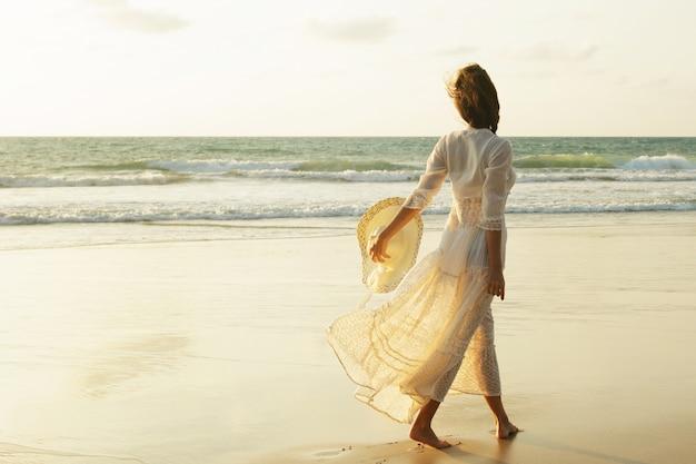 Femme portant une belle robe blanche marche sur la plage pendant le coucher du soleil