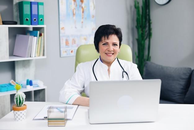 Femme portant une blouse médicale blanche avec stéthoscope regardant à l'avant