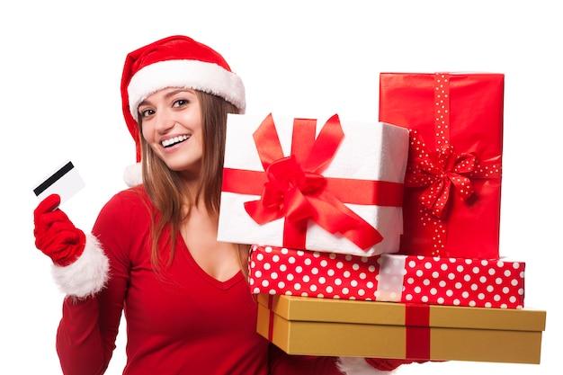 Femme portant bonnet de noel tenant des cadeaux de noël et carte de crédit