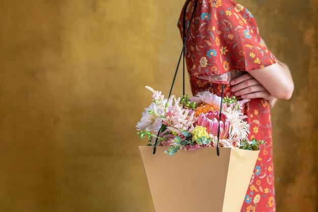Femme portant un bouquet de fleurs dans un sac en papier