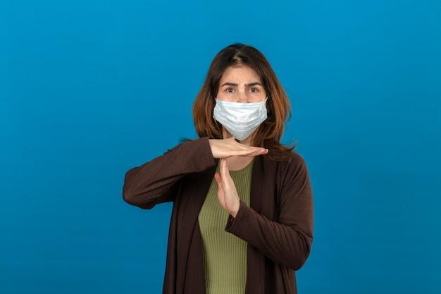 Femme portant un cardigan marron dans un masque de protection médicale à la fatigue faisant le geste de temps avec les mains debout sur un mur bleu isolé