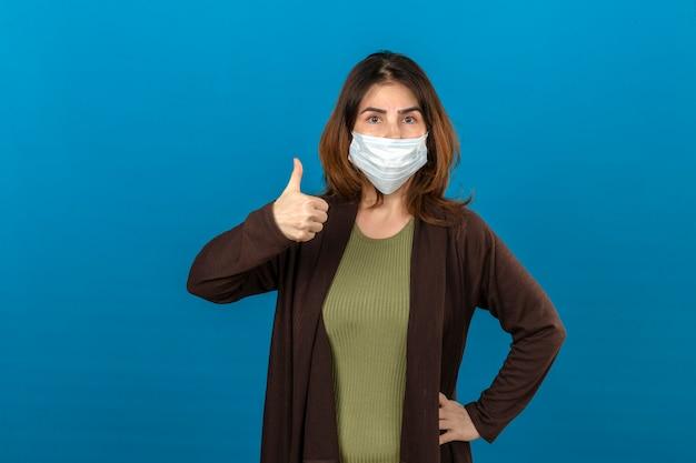 Femme portant un cardigan marron dans un masque de protection médicale montrant le pouce vers le haut sur un mur bleu isolé
