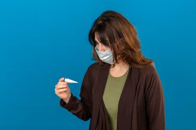 Femme portant un cardigan marron en masque de protection médicale à la recherche de thermomètre numérique à nerveux sur mur bleu isolé