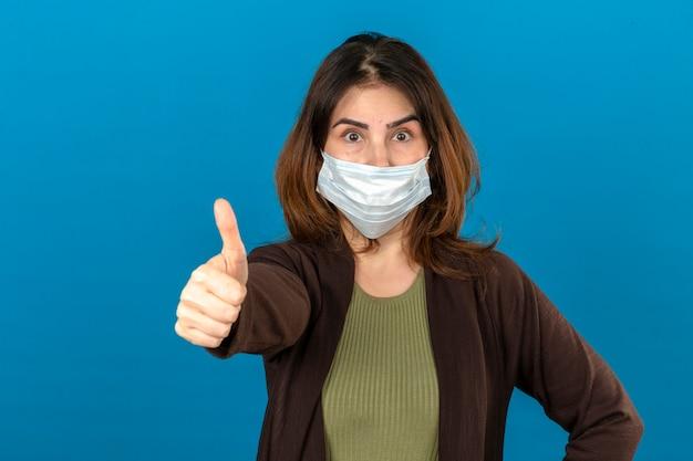 Femme portant un cardigan marron en masque de protection médicale à la surprise montrant le pouce vers le haut debout sur un mur bleu isolé