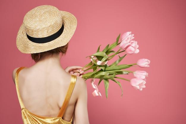 Femme portant un chapeau bouquet de fleurs vue arrière décoration fond rose