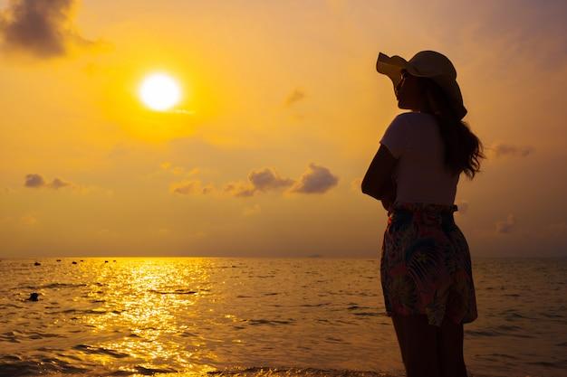 Femme portant chapeau debout sur la plage de la mer au coucher du soleil