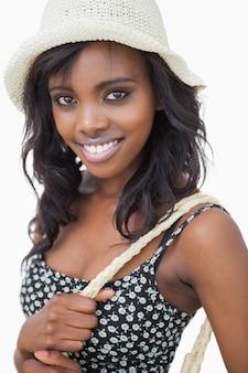 Femme portant chapeau d'été et robe de fleur noire sur fond blanc