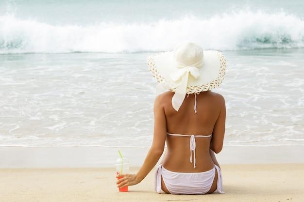 Une femme portant un chapeau à larges bords tient un verre de cocktail froid et est assise sur la plage