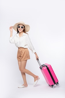 Femme portant un chapeau, des lunettes et des poignées de valises pour voyager