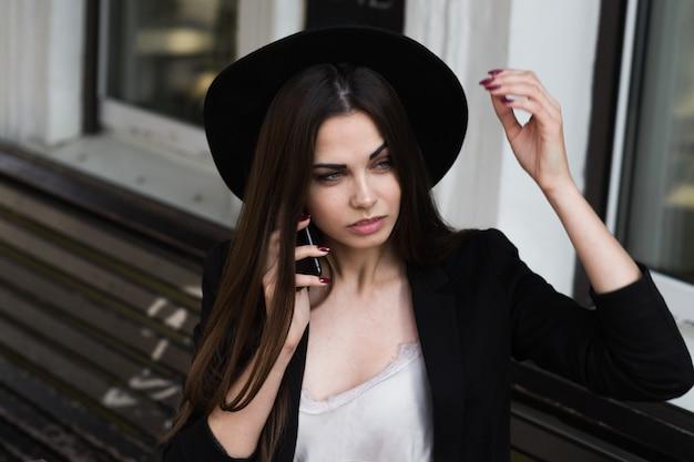 Une femme portant un chapeau noir et utiliser un téléphone portable