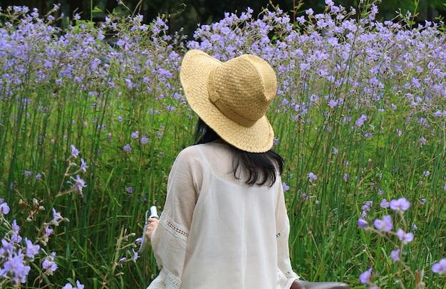 Femme portant chapeau de paille avec sa bicyclette en regardant beau champ de fleurs pourpre pastel
