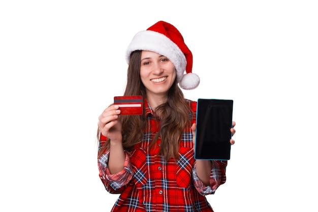 Une femme portant une chemise à carreaux et un chapeau de noël tient une carte et une tablette.