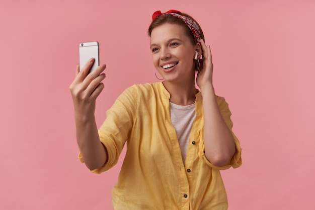 Femme portant une chemise jaune et un bandana rouge avec des bras gesticule au téléphone souriant côté émotion flirter sourire heureux heureux isolé posant sur rose