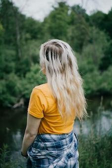 Femme portant une chemise jaune avec une veste bleue et blanche, debout sur le fond des arbres