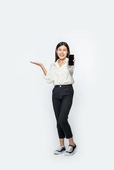 Une femme portant une chemise et tenant un smartphone