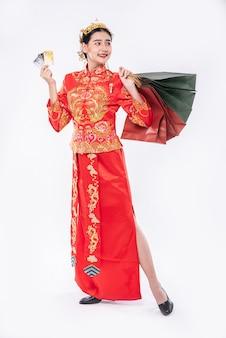 Une femme portant un costume cheongsam obtient beaucoup de choses en utilisant une carte de crédit au nouvel an chinois