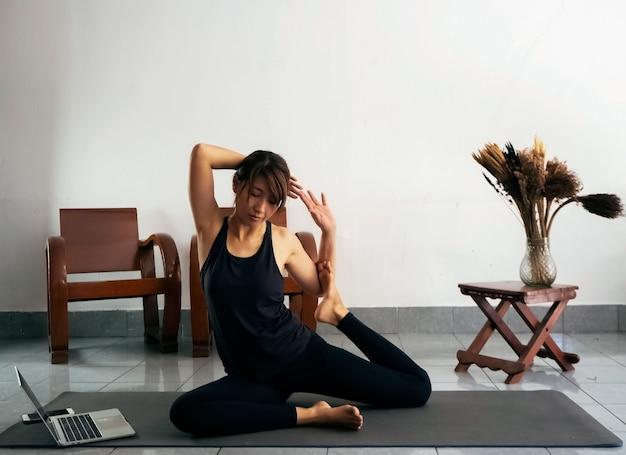 Femme portant un costume d'exercice, un corps strteching sur un tapis de yoga, un ordinateur portable sous forme d'apprentissage, à la maison