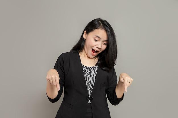 Une femme portant un costume noir pointe du doigt et regarde vers le bas avec une expression surprise avec une bouche béante