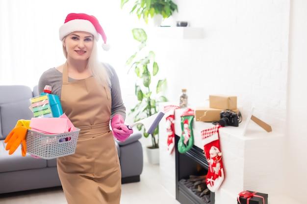Femme portant des décorations festives prêtes pour le nettoyage après noël