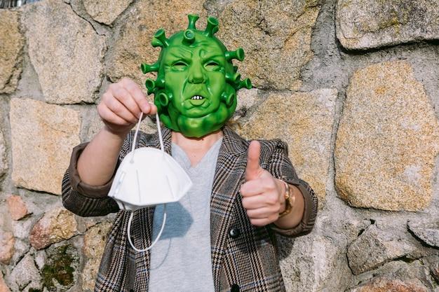 Femme portant un déguisement - masque de coronavirus covid-19 tenant un masque ffp2, levant le doigt ok