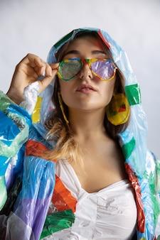 Femme portant du plastique sur un mur blanc. modèle féminin en vêtements et chaussures en ordures. mode, style, recyclage, concept écologique et environnemental. trop de pollution, on en mange et on en prend.