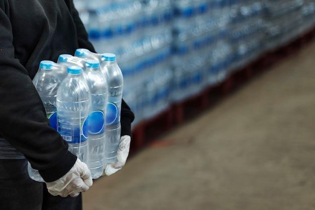 Femme portant de l'eau potable avec des mains gantées pendant la pandémie de coronavirus
