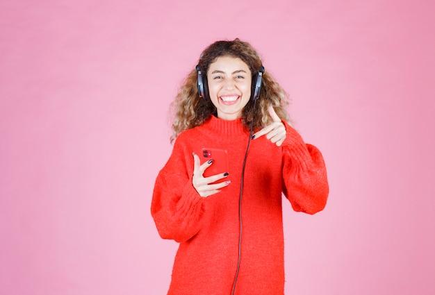 Femme portant des écouteurs écoutant sa liste de lecture sur smartphone et dansant.