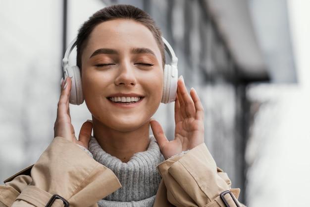 Femme portant des écouteurs à l'extérieur